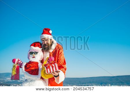 Snowman In Pink Wig, Mittens And Glasses With Shopping Bags