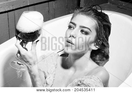 Closeup of pretty young sensual woman with wet hair sitting in white bath tab holding in hand drinking glass with red liquid with smoke as elixir of beauty indoor horizontal picture