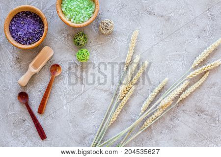 organic cosmetic set with wheat herbs and sea salt in bowl on stone table background flat lay