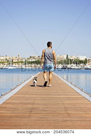 A man with a dog walking on the floating pier on a sunny day. Friendship and travel with dog