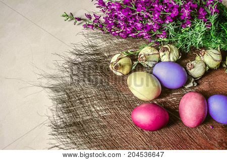 Brightly colored Easter eggs near the bouquet of wild flowers and dried buds of roses on a underlay of straw