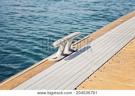 The metal bitt fairleads on a wooden pontoon and blue water