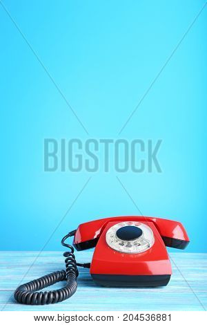 Red retro telephone on the wooden table