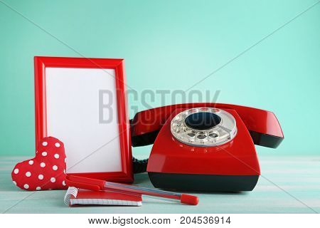 Red Retro Telephone With Photo Frame, Heart And Notebook On Wooden Table