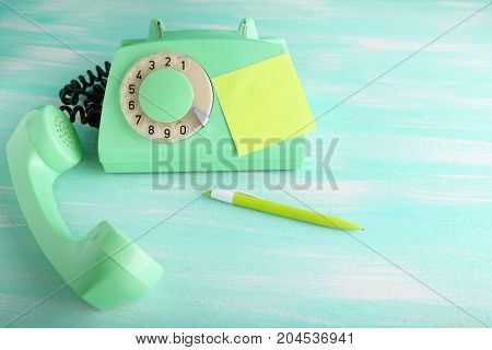 Green Retro Telephone With Sticky Note And Pen On Wooden Table