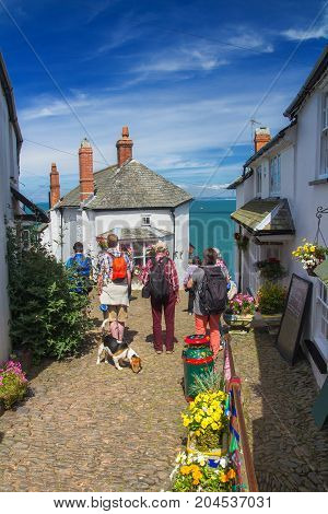 Several tourists stand on a paved path and admire the beauty of the village of Clovelli. This picturesque English village is located on the steep seashore in Devon. Tourists have a dog. Along the path there are many bright flowers. England