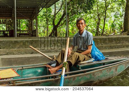 A Boat Guide At Trang An Unesco World Heritage Site In Ninh Binh, Vietnam