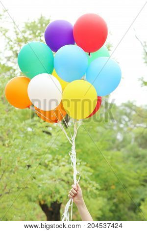 Hand holding colorful balloons in the park