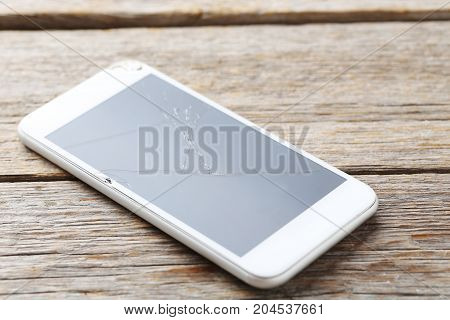 Broken smartphone on a grey wooden table