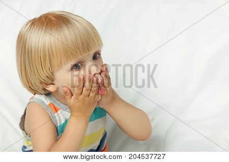 Surprised Little Boy Sitting In White Bed