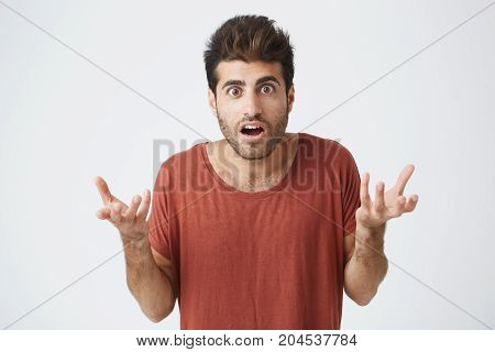 Young stylish spanish guy in red t-shirt with mouth wide opened, holding hands in surprised gesture shocked with his favourite football team loses in match. Body language.