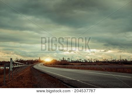 Empty Asphalt Road With Near The Lake With Cloudy Sky In Evening Light