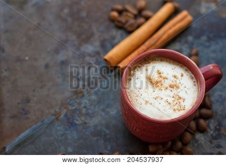 Hot chocolate with cinnamon stick on dark background