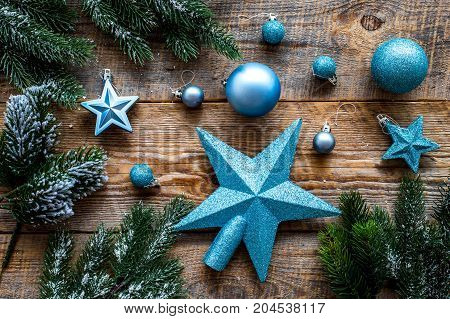 Star and balls for christmas tree near pine branches on wooden background top view.