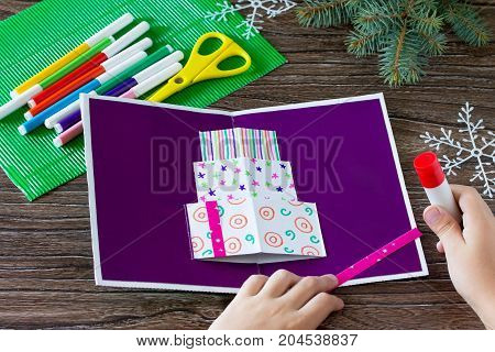 A child glues together a greeting card with Christmas presents. Made by own hands. Children's art project craft for children. Craft for kids.