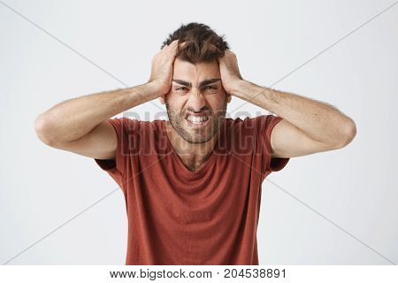 Angry good-looking caucasian male in red t-shirt having mad expressions, squeezing head with hands pissed of people around on work. Negative emotions