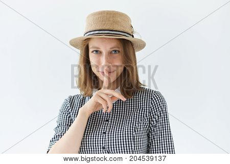 Studio shot of enigmatic beautiful romantic young freckled lady wearing collar dress and retro hat smiling mysteriously holding finger at her lips asking to keep something a secret. Body language