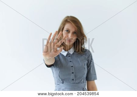 Body language. Refusal ban prohibition denial and rejection. Frustrated young European female in dress stretching out hand warning someone showing stop sign. Selective focus on woman's palm