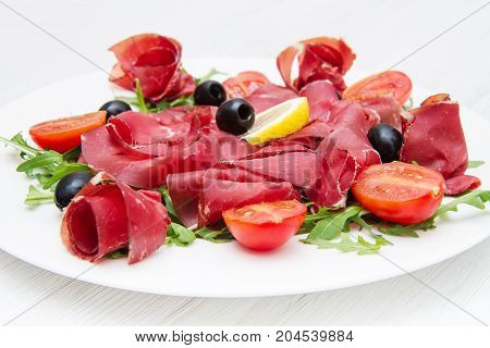 a dish of bresaola and aragula and black olives