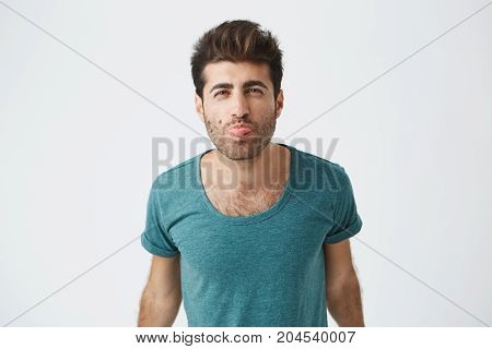 Studio portrait of funny mature spanish guy in blue t-shirt, playing fool showing his tongue and having fun indoors. Human face expressions