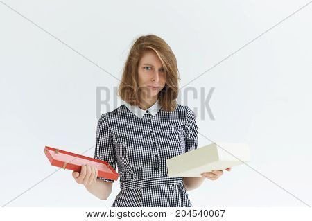 Portrait of attractive unhappy sad young Caucasian woman opening birthday present box disappointed about gift that she received. Negative human expressions emotions reaction and attitude