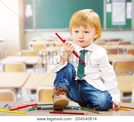 a little child handing colored crayons in the classroom