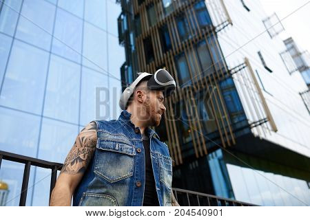 People science gaming simulation and augmented reality. Serious confident young man with stubble and stylish tattoos posing in urban surroundings using oculus rift headset for entertaining himself