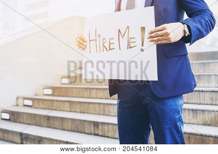 business man holding board with text hire me on business district business concept