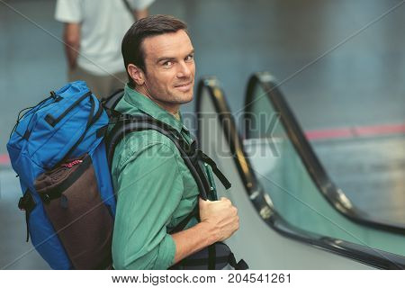 Summer adventure. Top view of adult positive guy with backpack is moving down on escalator at international airport. He is looking at camera with joy. Copy space in the right side