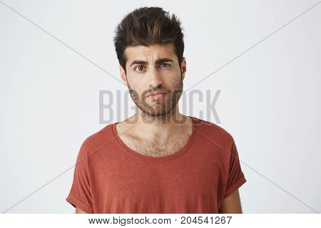 Skeptical looking spanish man in red t shirt with trendy hairdo and beard, looking in camera with suspicious and uncertain expression, listening his girlfriend story from last night