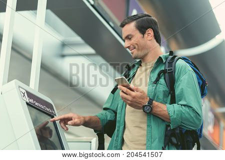 Modern device. Low angle of cheerful adult man with backpack is holding mobile phone and looking at screen of self-service kiosk while doing check-in for his flight at international airport