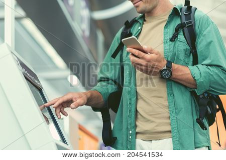 Confirm flight information. Low angle close-up of hands of male with backpack is standing with smartphone and using self-service check-in kiosk at international airport building