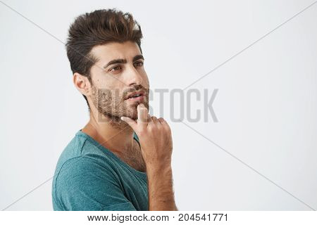 Close up studio portrait of handsome spanish male in blue tshirt, looking up with thoughtful expression, thinking about dinner for today. studio portrait. Human face expressions.