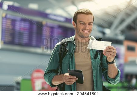 Checking flight ticket. Cheerful stylish man with backpack is looking at ticket with smile while standing in international airport against electronic timetable