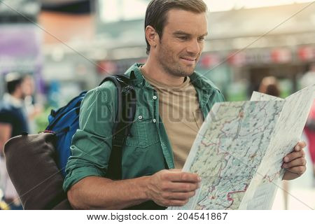 Travel itinerary. Joyful bristled man is looking at map with curiosity while standing with backpack at modern airport