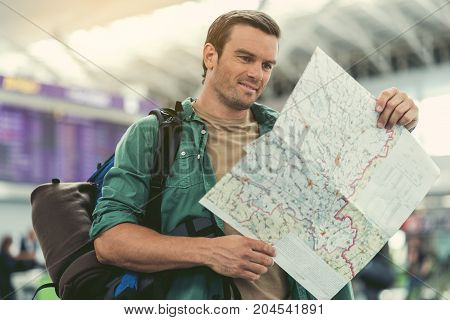 Summer trip. Cheerful adult guy with backpack is viewing world map with interest while waiting for his flight. Electronic timetable on the background