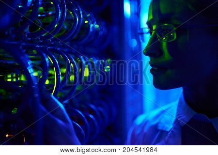 Closeup portrait of beautiful  female face by wire cables of server cabinet in neon light