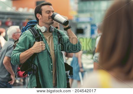 Fresh coffee. Cheerful man with backpack and headphones on his neck is standing at international airport and drinking espresso with pleasure while waiting for his flight. Copy space