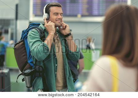 Enjoying song. Selective focus of adult man is listening to music through headphones while standing with closed eyes at international airport. He is expressing pleasure. Copy space