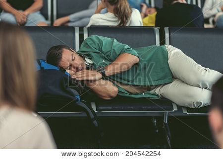 Delayed flight. Exhausted man with headphones on his neck is sleeping on bench at international airport with passengers on background