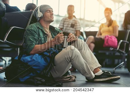 Relaxing melody. Selective focus of stylish adult guy is sitting on floor of international airport with closed eyes and listening to music through headphones while drinking fresh espresso