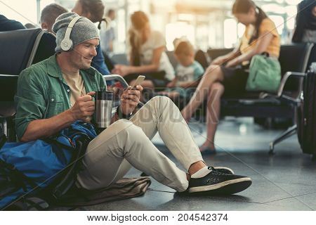 Wi-Fi zone. Cheerful man is looking at screen of mobile phone while listening to music through headphones. He is drinking coffee while sitting on floor in airport lounge. Copy space