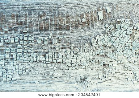 Peeling paint on the wooden texture background. Closeup of peeling paint texture on the wooden texture background. Texture of peeling paint on the wooden texture surface. Peeling paint texture.Texture background of peeling paint