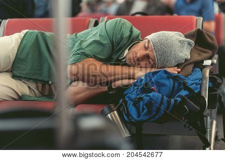 Need rest. Tired young guy is lying on seats in airport lounge and sleeping on his backpack while waiting for his flight
