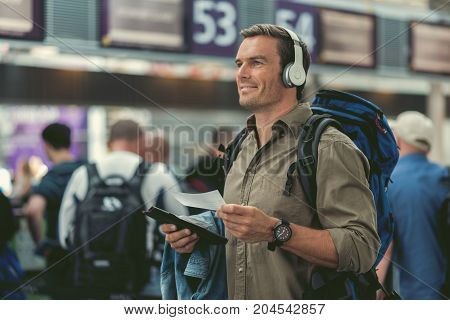 Life is good. Joyful young traveler is holding his tickets and looking aside with smile while listening to music through headphones. Copy space in the left side