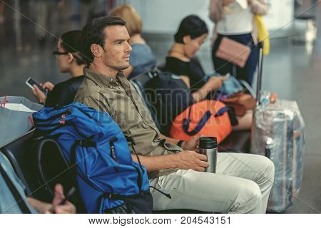 Feeling bored. Profile of serious young bristled man is sitting on seat at airport lounge and looking aside thoughtfully while drinking coffee. Passengers are on background