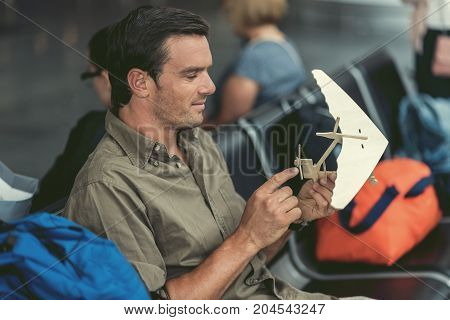 Back to childhood. Profile of positive adult man is playing with wooden model of hang glider while sitting on bench at airport lounge. People on background