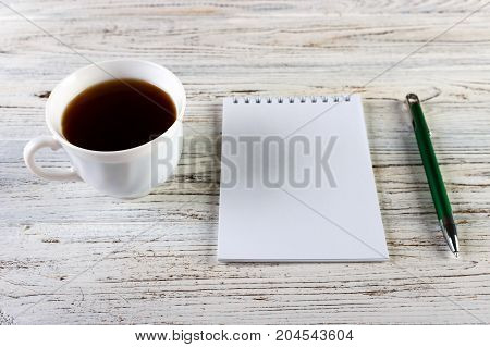 Cup of coffee with notebook on wooden desk Top view copy space