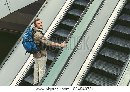 Top view of young cheerful man with backpack is moving up on staircase at international airport. He is looking at camera with smile. Copy space in the right side
