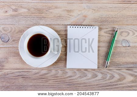 Blank notepad and pencil with cup of coffee on office wood table background. Business concept with copy space for any desing
